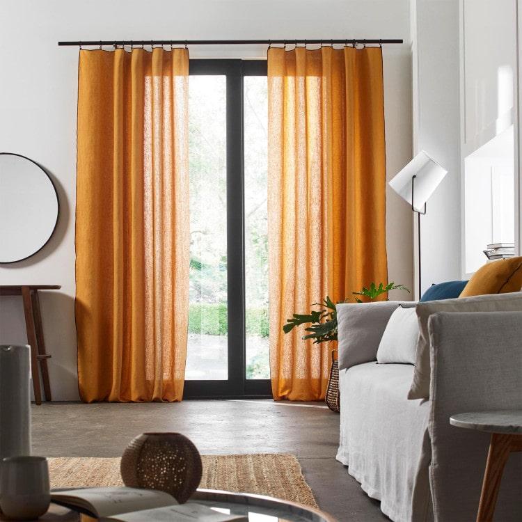 salon gris avec sol en béton et rideaux légers orange