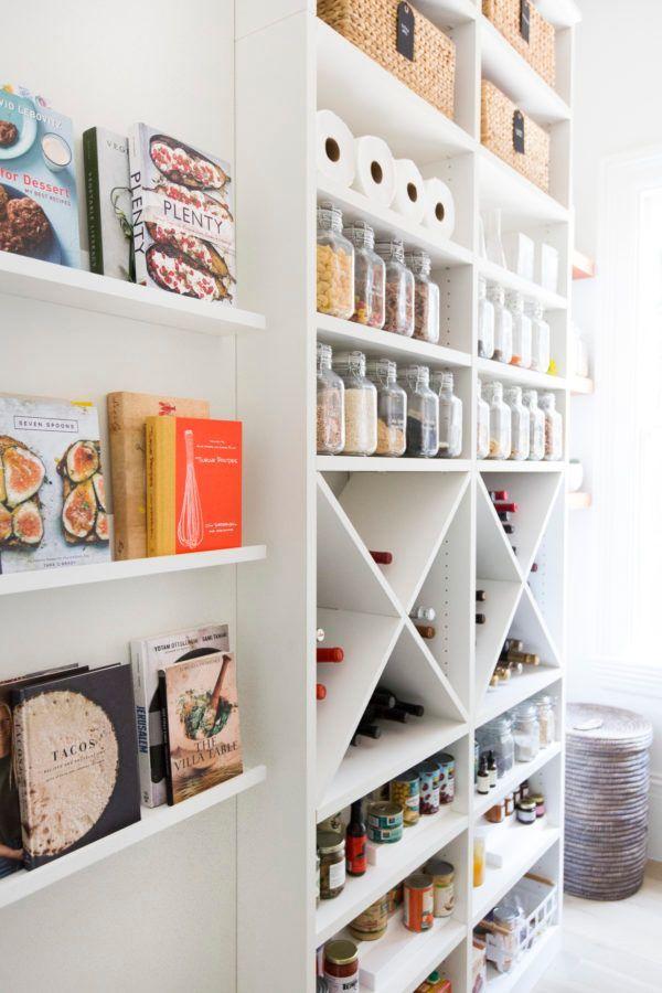 livres de cuisine et condiments en bouteilles et bouteilles de vin rangés dans un cellier en croisillon