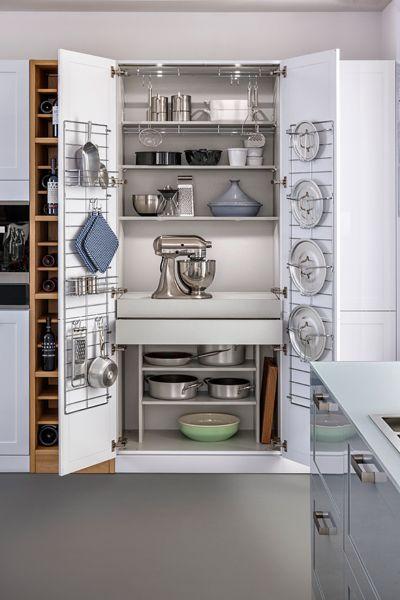 casseroles et robots de cuisine métalliques rangés dans un cellier blanc