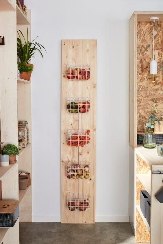 fruits et légumes rangés dans des paniers métalliques accrochés à une planche en bois