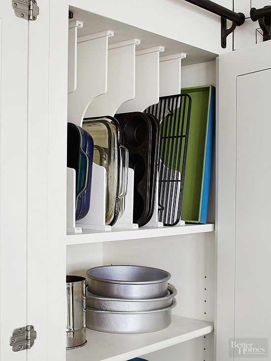 plats et moules de cuisine rangés dans un placard blanc