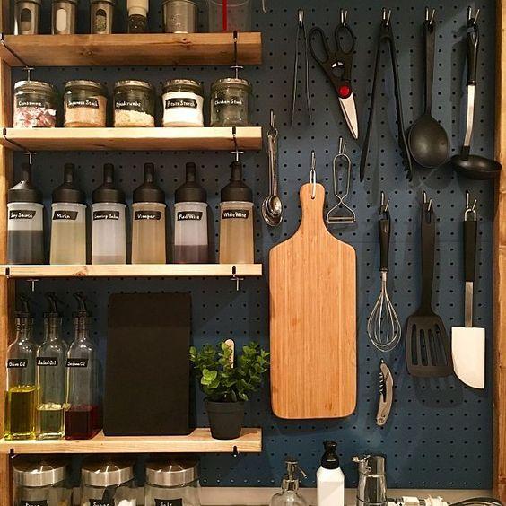 étagères de cuisine en bois pleines avec ustensiles accrochés à une crédence métallique bleu