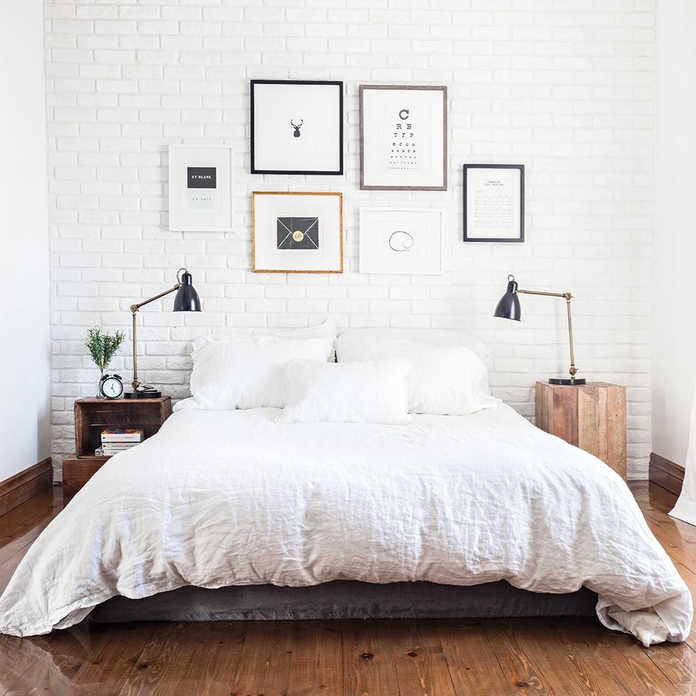 lit-avec-draps-blancs-et-cadres-sur-mur-blanc