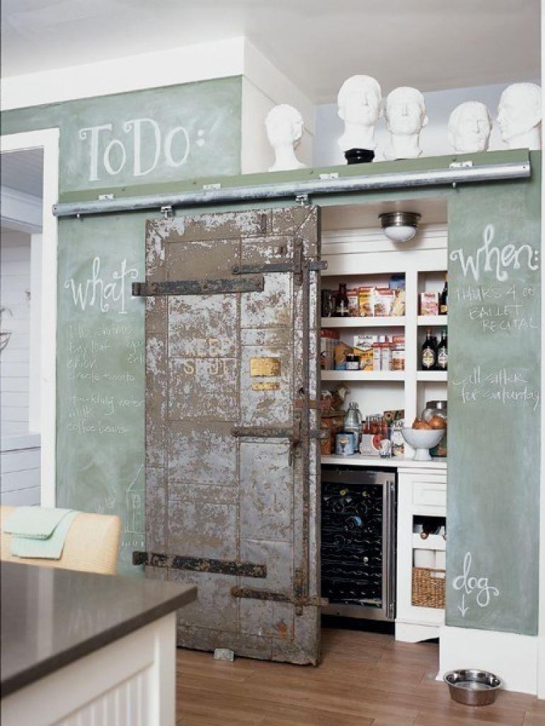 porte métallique cachant un cellier de style vintage derrière mur peint en vert