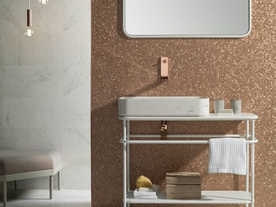 Une salle de bains au sol marbré et dont le mur est incrusté de mosaïque en rosé doré
