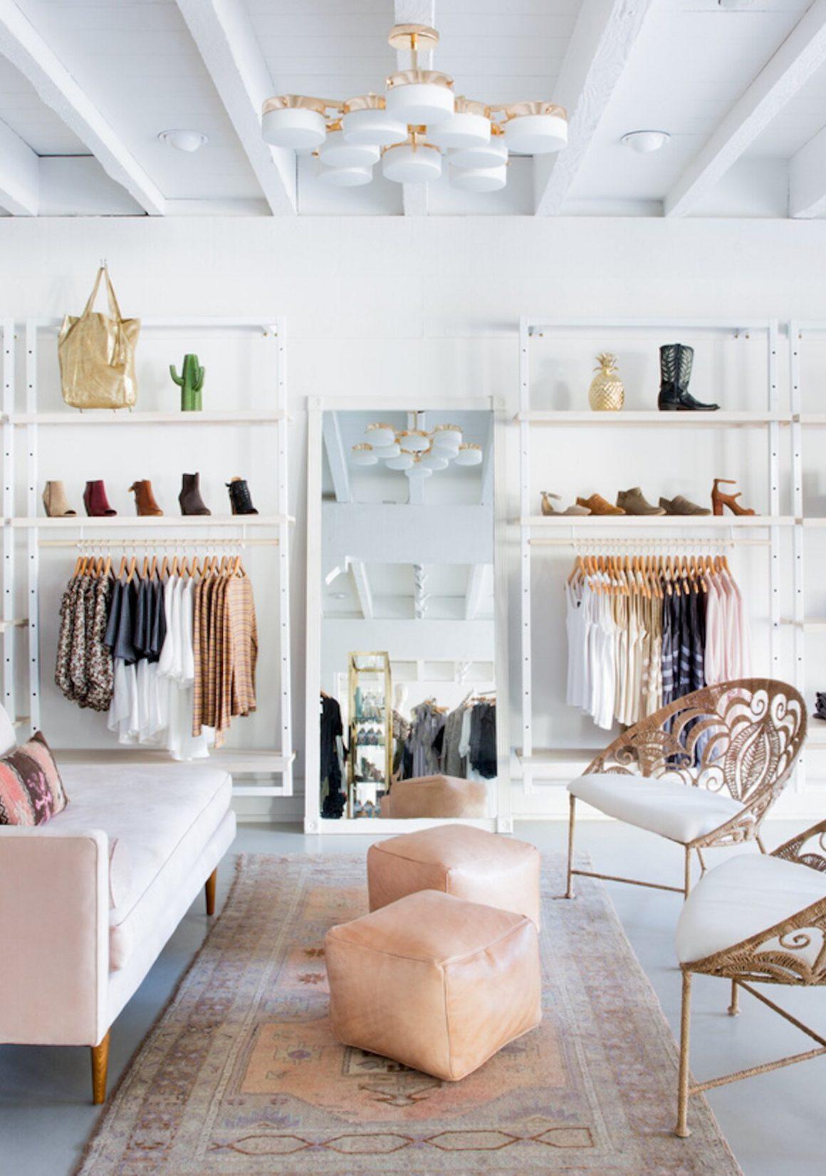 coin salon contemporain avec canapé rose et fauteuils en acier doré dans un magasin de vêtements