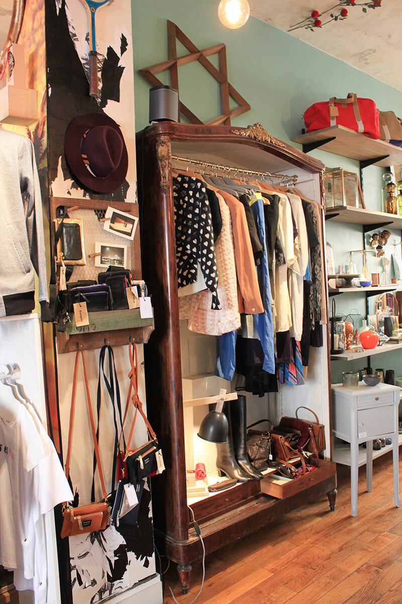 magasin de brocantes avec des vêtements rangés dans de vieux meubles vintage