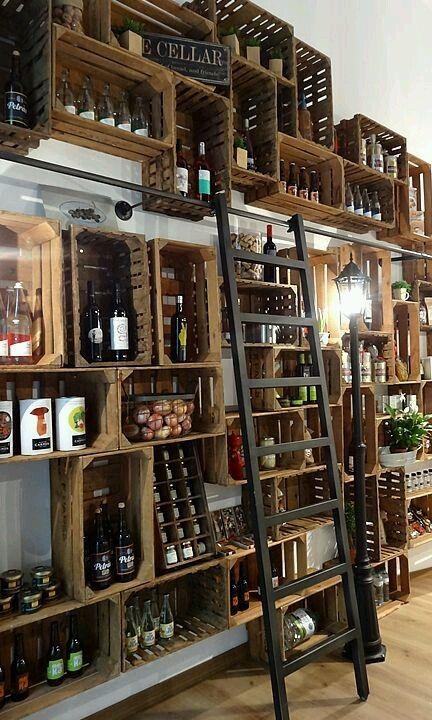 bouteilles de vin et pots de nourriture rangés dans des caisses de vin accrochées au mur d'un magasin