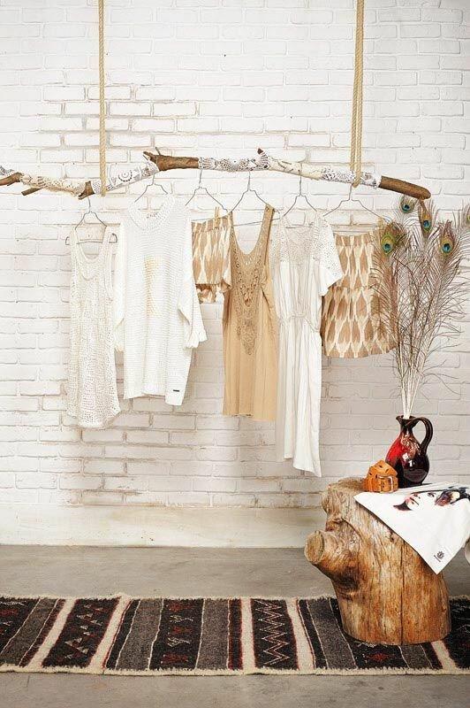 vêtements sur des cintres accrochés à une branche d'arbre suspendue avec des cordes