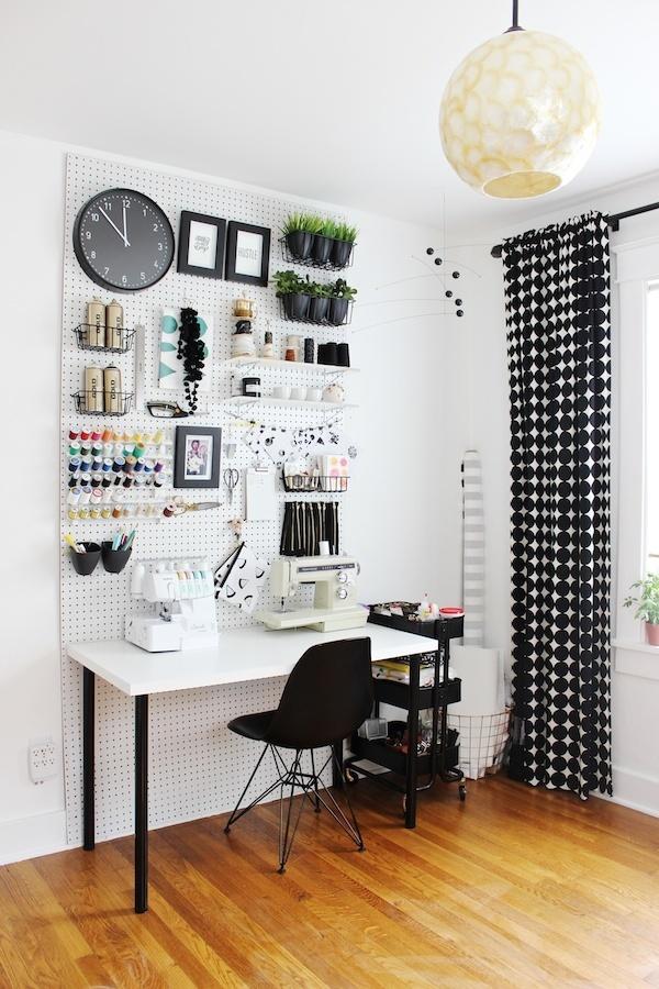 pièce aménagée en bureau avec mobilier noir et blanc et panneau mural en métal pour organiser des objets déco et des fournitures