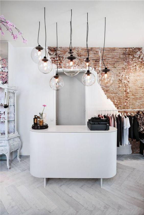 luminaires ronds suspendus au dessus d'un comptoir blanc dans une boutique de vêtement