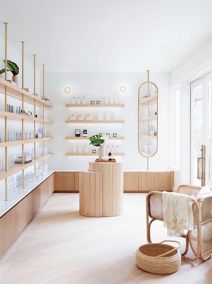 aménagement magasin minimaliste avec étagères beiges peu profondes et mobilier en bois et osier