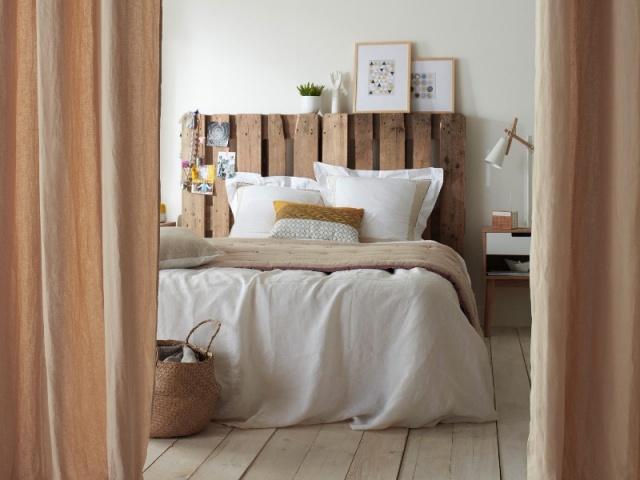 chambre adulte rustique avec une tête de lit en palette et des draps de lit blancs