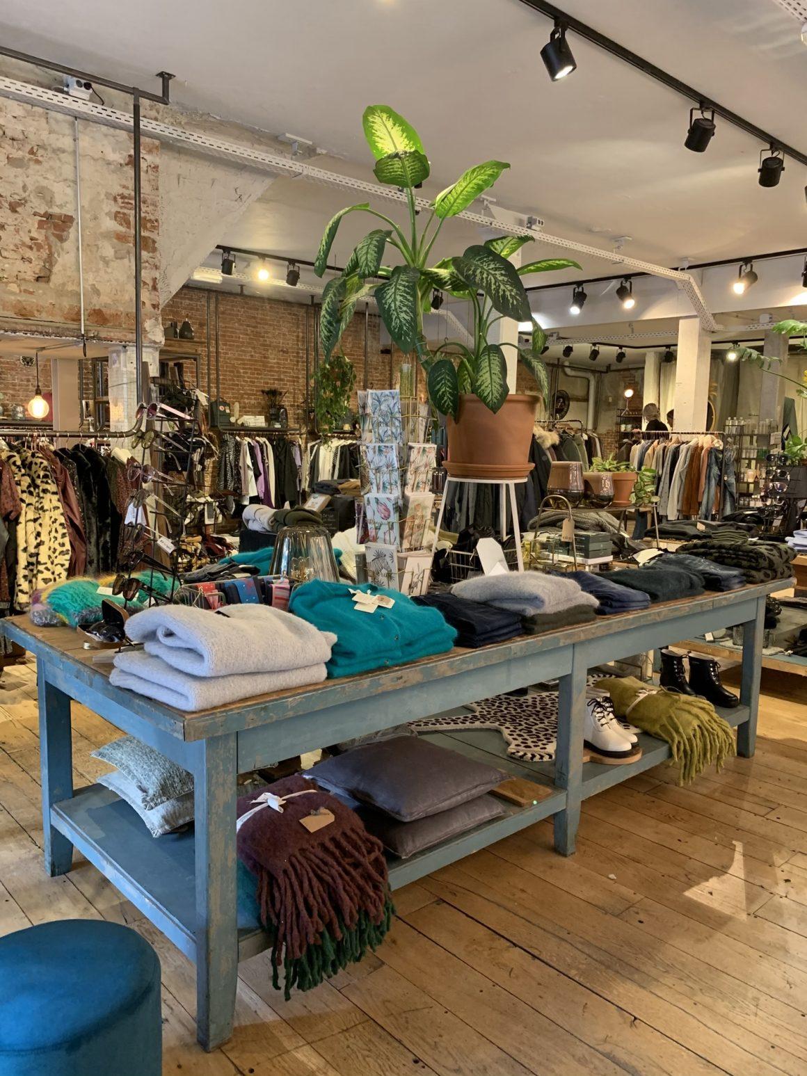 large table en bois peint en bleu accueillant des vêtements dans un aménagement magasin