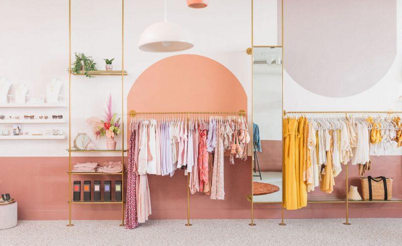 vêtements de couleurs sur portants en métal doré dans une boutique aux murs roses et saumon