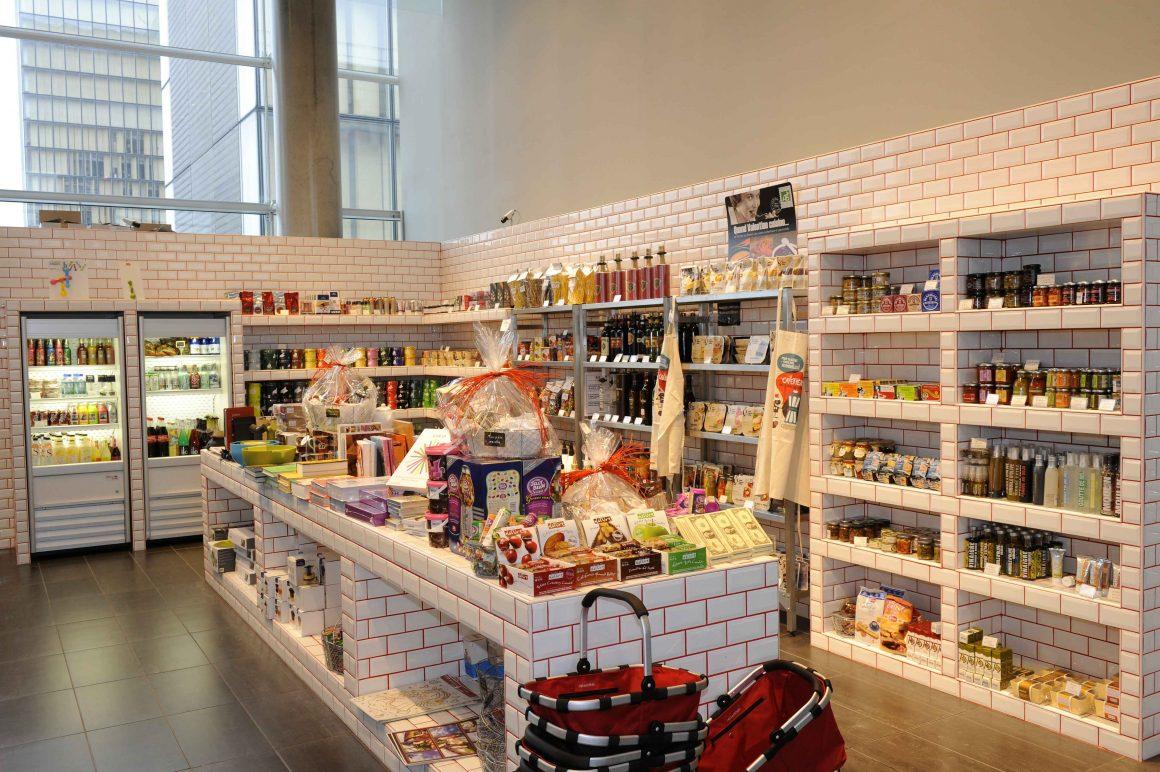 magasin de nourriture avec des étagères et des tables couvertes en carreaux de faïence blanche