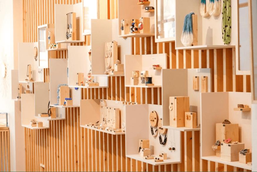 colliers et pendentifs exposés sur des étagères en bois sur un mur de boutique de bijoux