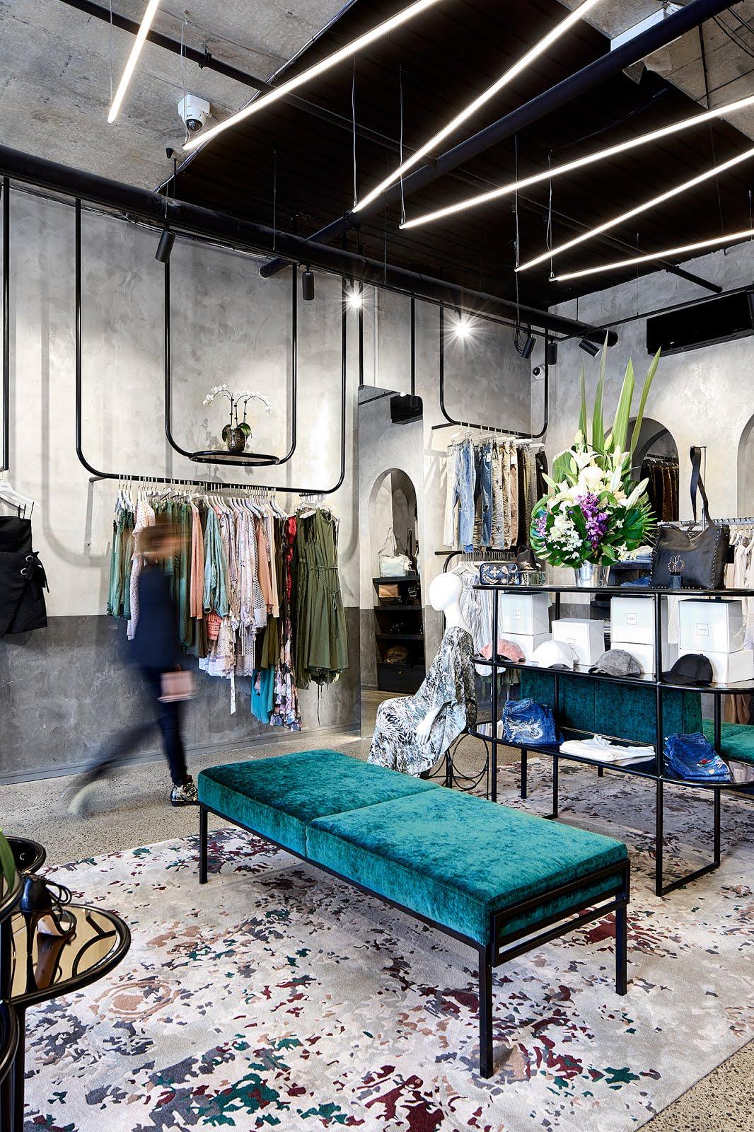 banquette en velours vert émeraude au milieu d'une boutique de vêtements aux mures en béton ciré