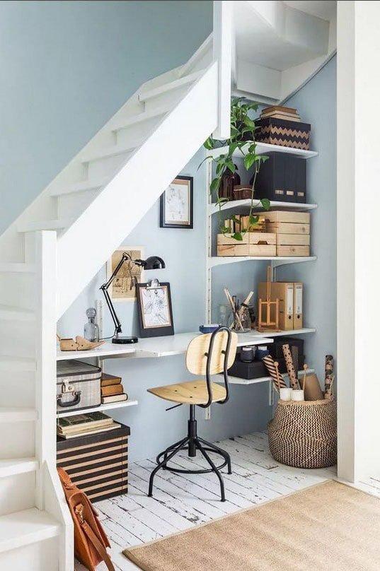 un bureau fonctionnel avec des étagères nichées sous un escalier en bois blanc