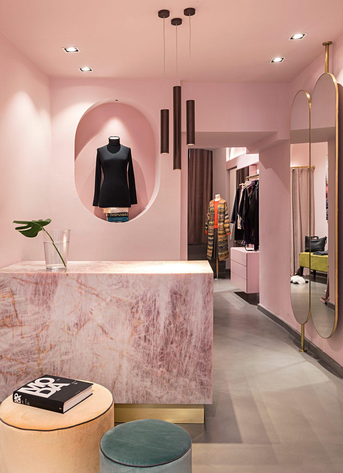 murs de boutique de vêtements peint en nuances de rose avec un comptoir en marbre et des miroirs à contours dorés