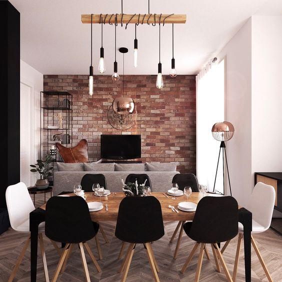 salon de style industriel avec des luminaires suspendues et un mur couvert de papier peint effet briques rouges