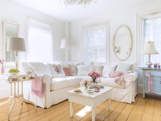 un grand canapé classique en blanc décoré de coussins roses et blancs dans une pièce classique au mobilier en bois