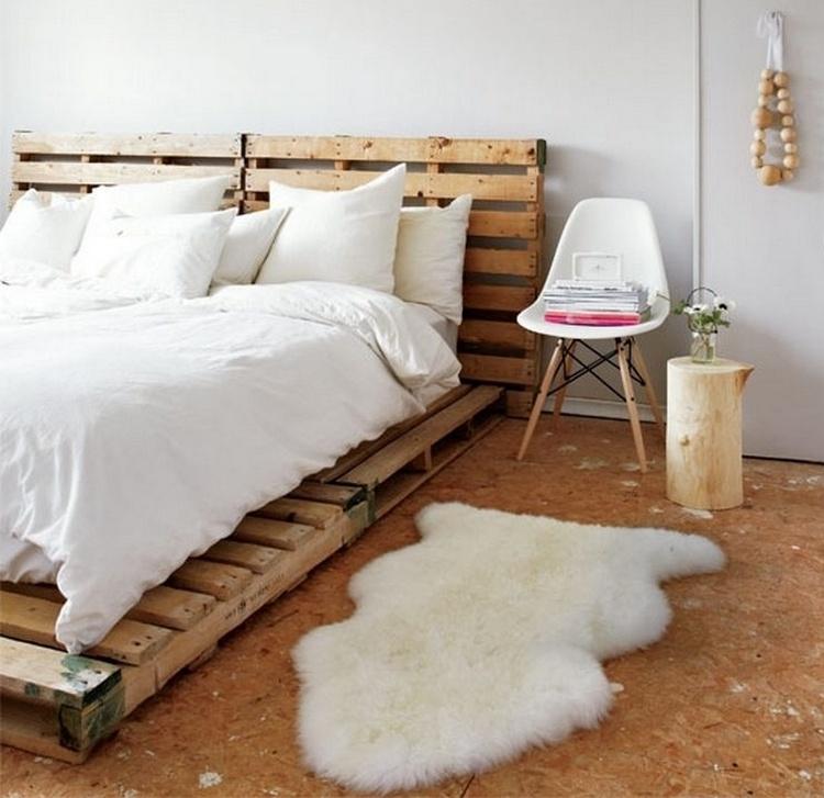 un lit adulte DIY en palettes en bois dans une chambre aux matériaux bruts