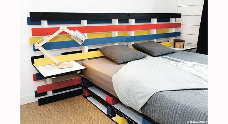 une tête de lit en bois en différentes couleurs dans une chambre de style bord de mer