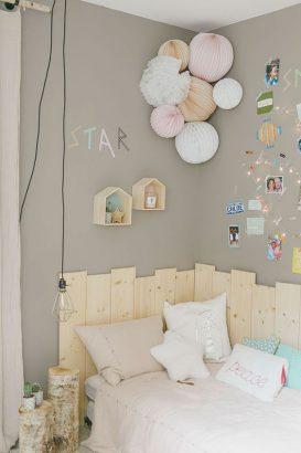 murs chambre enfant décorés de stickers et illustrations au dessus d'un lit entouré de palette en bois