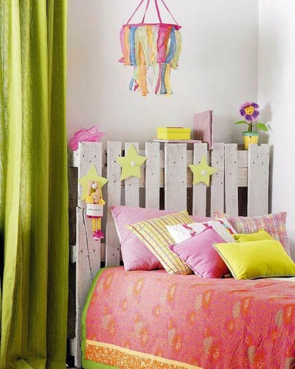 chambre enfant colorée avec des draps et rideaux en vert et rose et tête de lit en palette