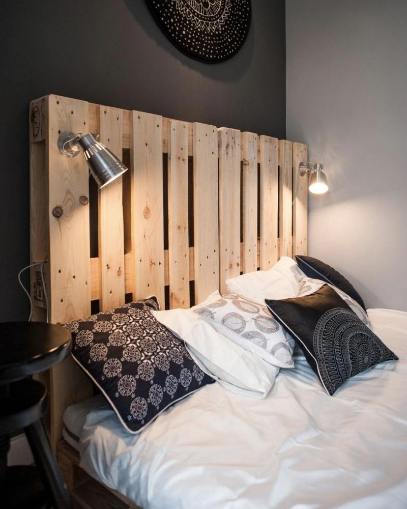 veilleuses lumineuses accrochées à une large tête de lit en palette de bois clair