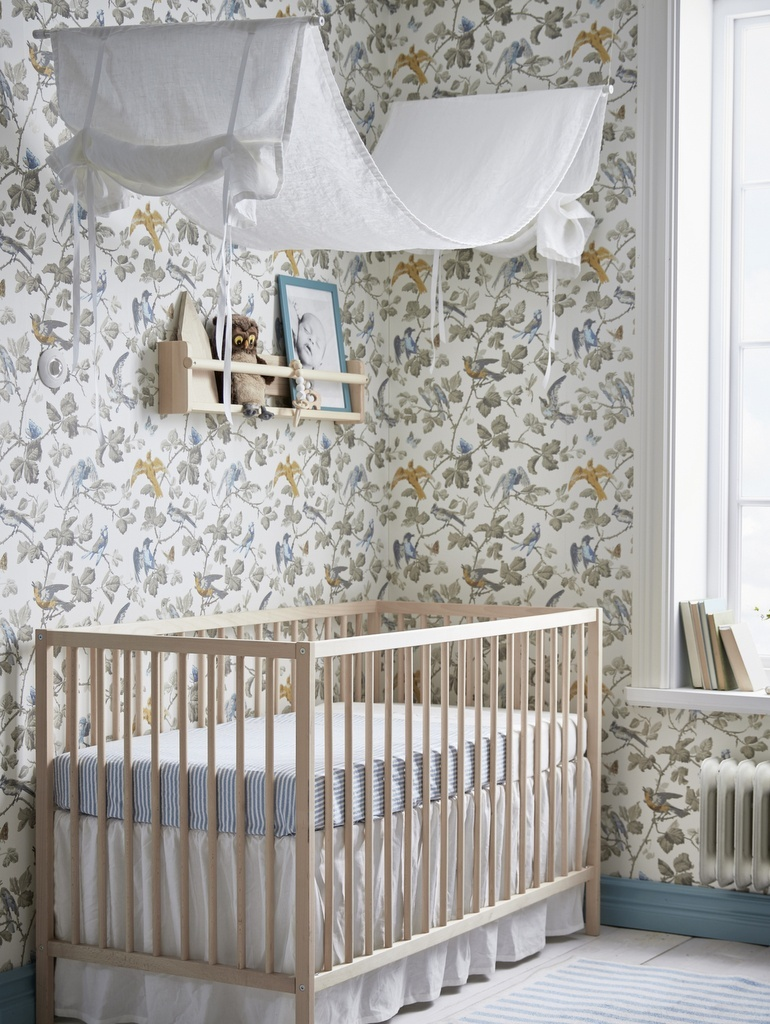 papier peint fleuri couvrant les murs autour d'un berceau en bois dans une chambre bébé