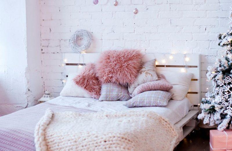 tête de lit en palette blanche avec des coussins roses sur le lit et une guirlande lumineuse dessus