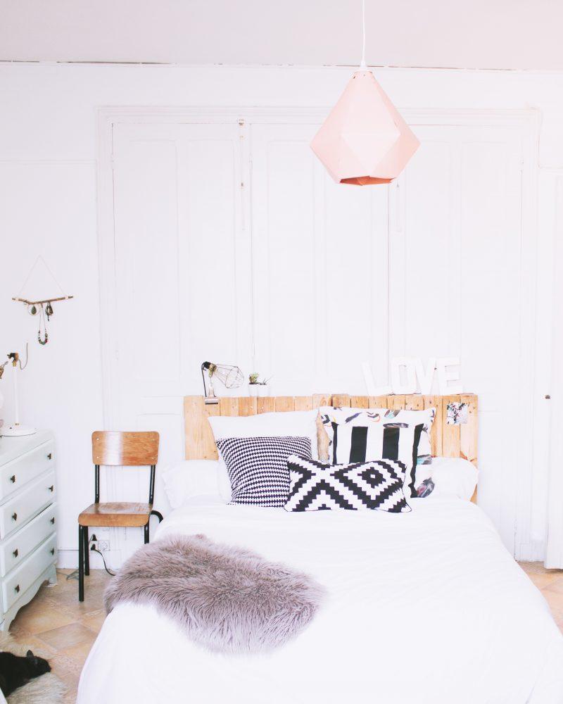 chambre adulte blanche avec mobilier vintage et tête de lit en palette en bois recyclé