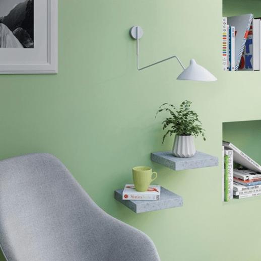 étagères minimalistes disposées en escalier sur un mur vert pastel pour une déco printemps de salon