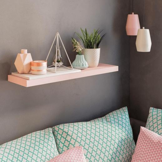 coussins à motifs géométriques verts en dessous d'une étagères rose portant des objets déco
