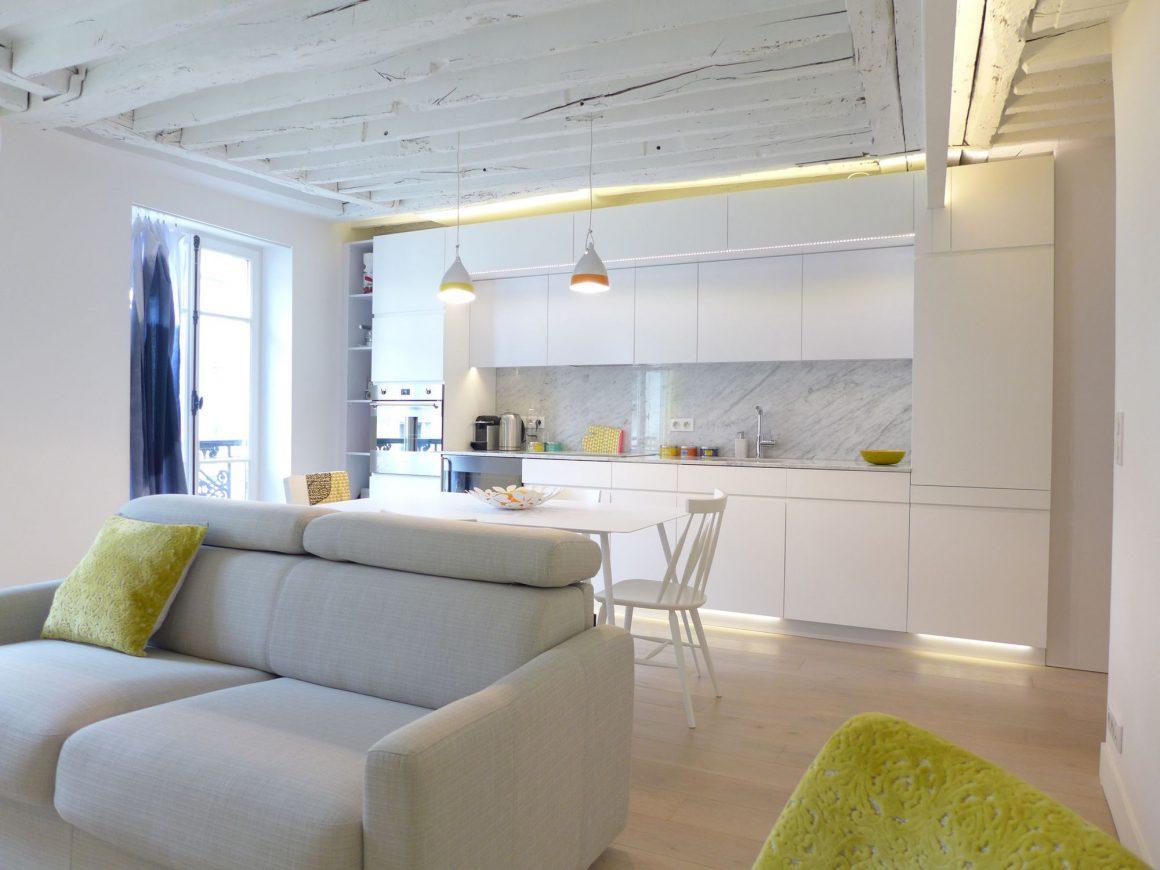 cuisine encastrée blanche dans un espace ouvert avec canapé moderne gris