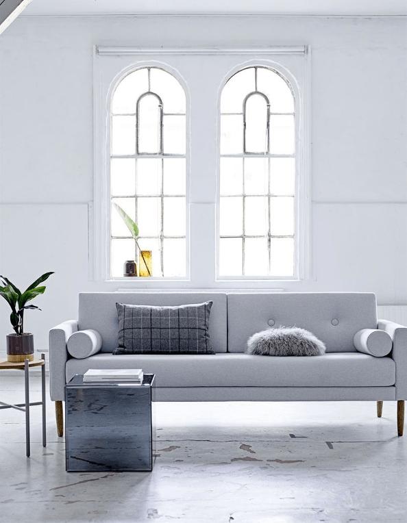 canapé moderne gris dans une pièce lumineuse à fenêtres larges