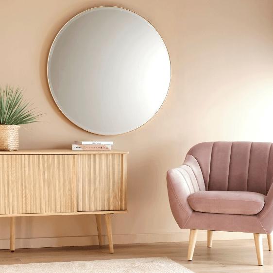 miroir rond accroché à un mur saumon a côté d'un fauteuil rose