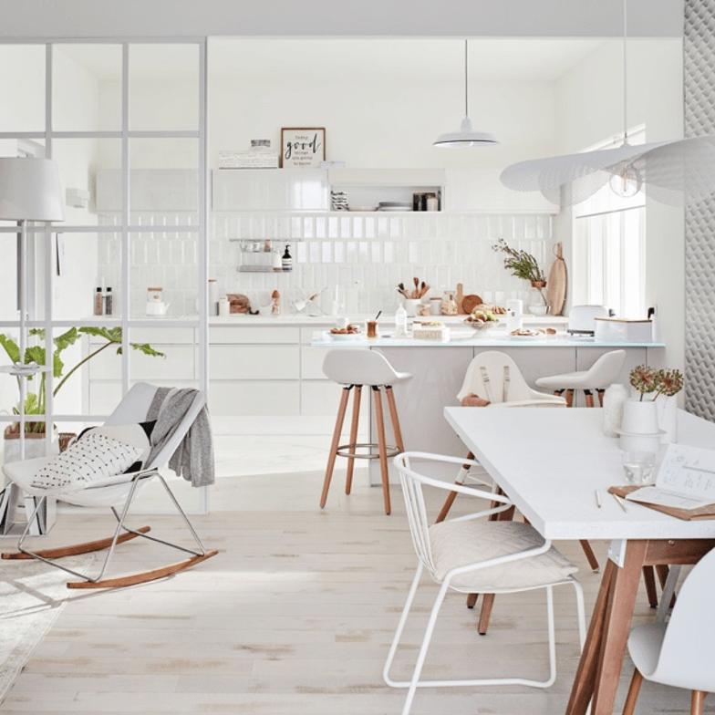 cuisine scandinave entièrement blanche ouverte sur une salle à manger au mobilier clair