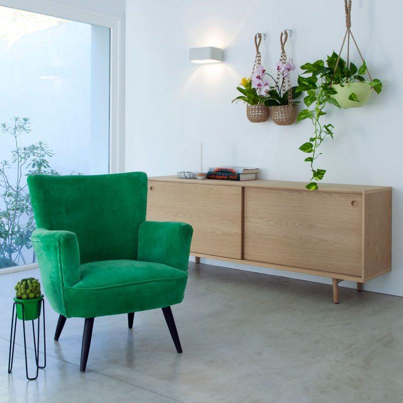 fauteuil vert émeraude et une console en bois pour ajouter une déco printemps à cette pièce