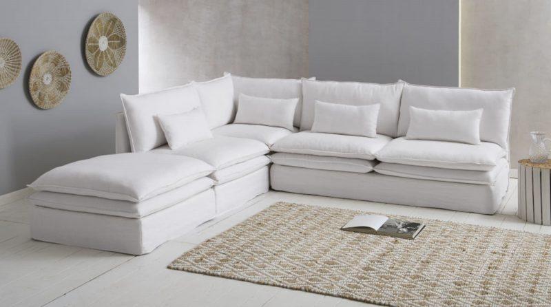 large canapé d'angle blanc en lin dans un salon à tapis berbère