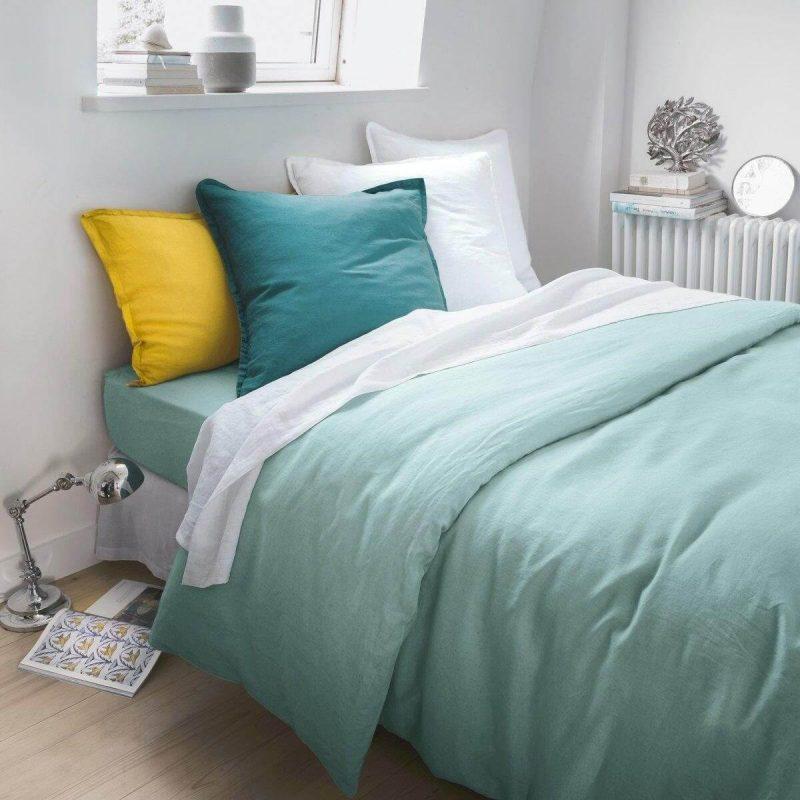 linge de lit et coussins verts et blancs sur un lit minimaliste