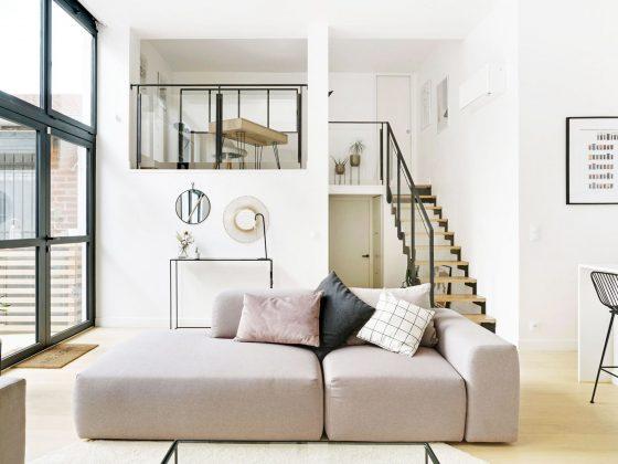 aménagement mezzanine derrière verrière accessible par des escaliers en bois dans une grande pièce lumineuse