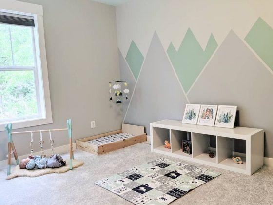 chambre bébé montessori de couleurs pastel avec graphiques au mur