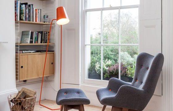 coin lecture cocooning avec fauteuil et repose pieds sous un lampadaire