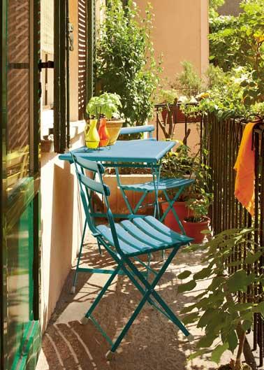 table et chaises métalliques bleues sur un balcon ensoleillé