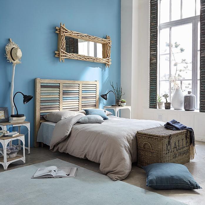 chambre à coucher bleue style bord de mer avec panier en osier et meubles en bois flotté
