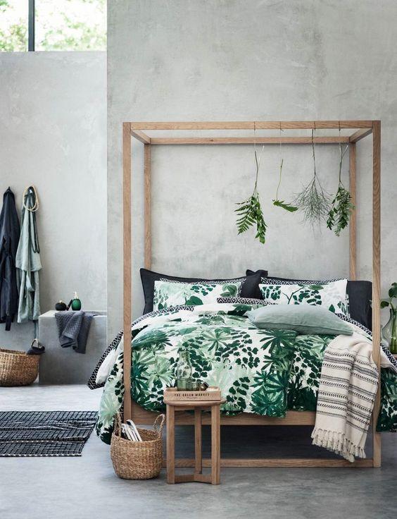chambre aux murs en béton avec lit baldaquin et linge de lit à motif forêt tropicale