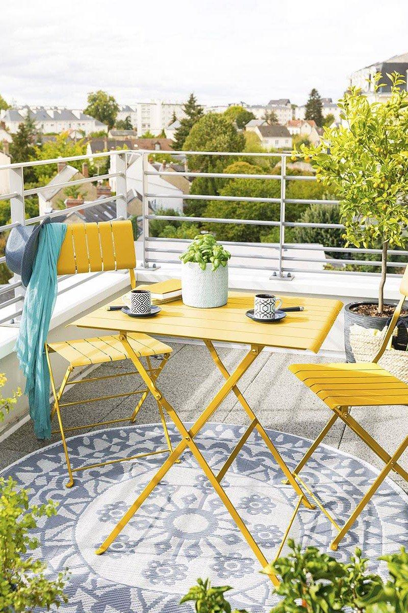 table et chaises métalliques jaunes de jardin pliables installées sur un balcon pour une déco été
